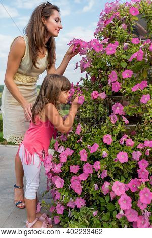 Woman Mom In Summer In City With A Little Daughter, A Girl 5-6 Years Old, Sniffing Flowers On Verand