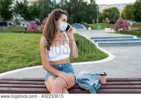 Female Woman City Summer Medical Mask, Sits On Bench, Cup Of Coffee Tea. Talks On Phone, Listens Voi