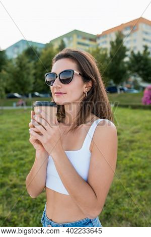 Happy Woman In Sunglasses, In Summer Park Holds Cup With Coffee Tea In Her Hands, Enjoys Rest Smell