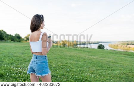 Beautiful Athletic Girl In Summer Outdoors, Holding Cup With Coffee Tea In Hands, Relaxation Enjoyme