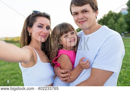Happy Family Man Dad Woman Mom, Hug Baby Daughter And Hold Her Arms. Taking Pictures Smartphone, Hap