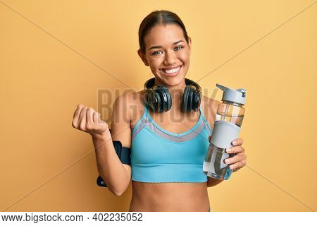 Beautiful hispanic woman wearing sportswear drinking bottle of water screaming proud, celebrating victory and success very excited with raised arm