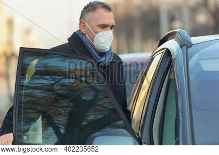 Mature man wearing a face mask during the covid-19 pandemic gets into a car