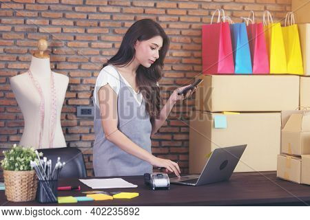 Young Woman Tailor With Laptop Is Answering Emails, Business Woman Entrepreneurial Success . Sales O
