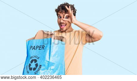 Young handsome man with curly hair holding recycling wastebasket with paper and cardboard smiling happy doing ok sign with hand on eye looking through fingers