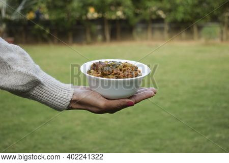 Undhiyu Or Oondhiyu A Traditional Famous Gujarati Cuisine Dish Item Served In A Bowl. Female Hand Ho