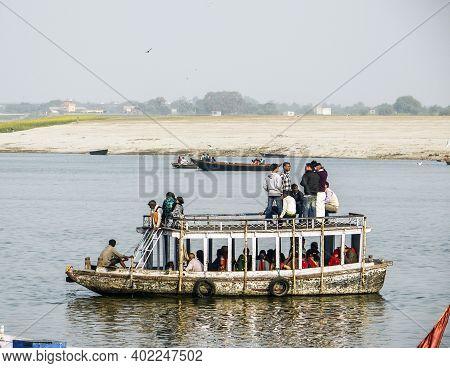 Varanasi, India - December 11, 2011: People Cross The River Ganges On A Ferry In Varanasi, India. Fe