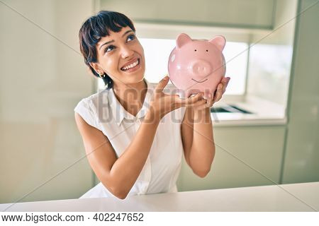 Young brunette woman smiling happy showing proud piggy bank with savings