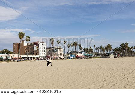 Venice, Usa - Mar 5, 2019: People Enjoy Scenic Beach Promenade With Palms And Colorful Houses At Ven