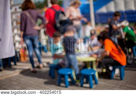 People , Family In A Recreation Park. Abstract Blur People Picnic In Public Park With Family Or Frie