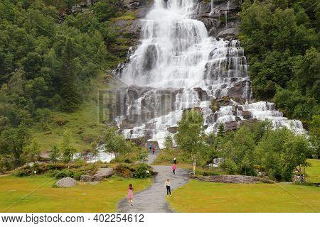 Skulestadmo, Norway - July 30, 2020: People Visit Tvindefossen Waterfall In Skulestadmo, Norway. Nor