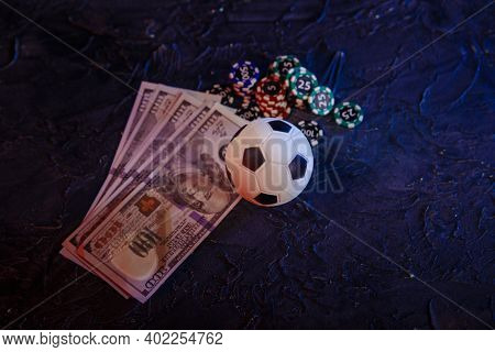 Gambling Chips, Soccer Ball And Dollar Banknotes On A Grey Background. Online Gambling And Betting C