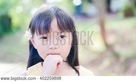 Cute Little Asian Girl Tuck A White Flower In His Ear And Look At The Camera