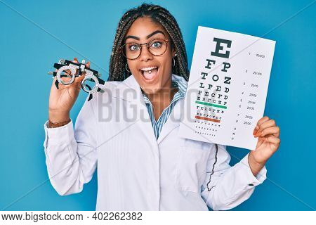 Young african american optician woman with braids holding optometry glasses and medical exam celebrating crazy and amazed for success with open eyes screaming excited.
