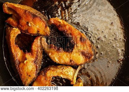 Fried Fish Snacks On Frying Pan. Pieces Of Fried Fish. Pieces Of Fried Fish In Boiling Oil. Pieces O