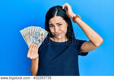 Beautiful young woman holding dollars confuse and wondering about question. uncertain with doubt, thinking with hand on head. pensive concept.
