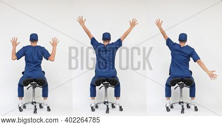 Male medical professional stretching arms and back sitting on mobile saddle - back view