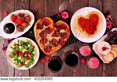 Home Cooked Valentines Day Dinner. Above View Table Setting On A Dark Wood Background. Heart Shaped