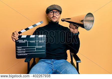 Handsome man with tattoos holding video film clapboard and louder relaxed with serious expression on face. simple and natural looking at the camera.