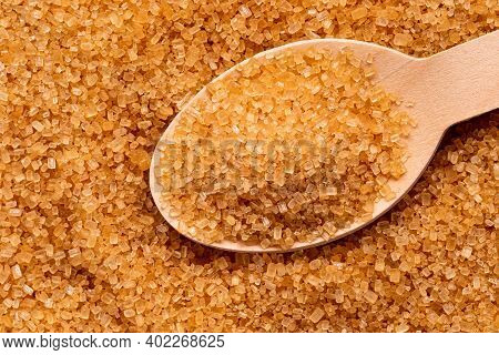 Wooden Spoon Full Of Light Brown Granulated Sugar On Top Of Brown Granulated Sugar.