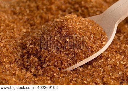 Wooden Spoon Full Of Dark Brown Granulated Sugar On Top Of Brown Granulated Sugar.