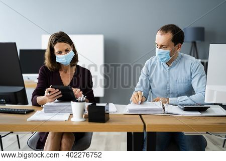 Chartered Tax Accountants With Calculators In Face Masks