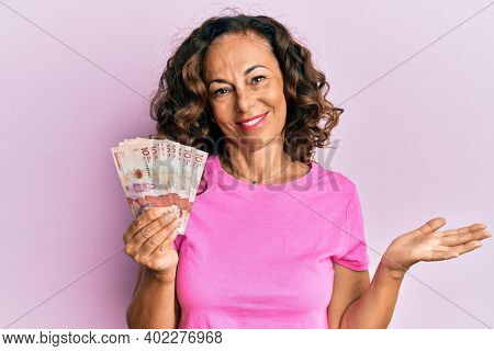 Middle age hispanic woman holding 10 colombian pesos banknotes celebrating achievement with happy smile and winner expression with raised hand