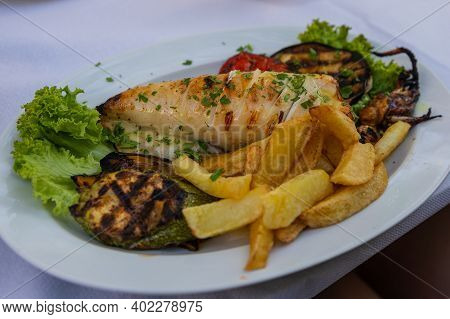 Grilled Fresh Squid On White Plate With Chips, Lettuce And Grilled Vegetables. Traditional Mediterra