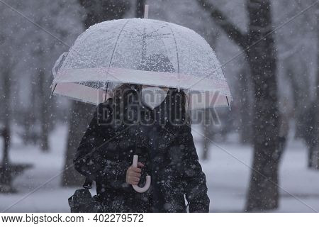 Madrid, Spain - January 07, 2021: A Young Girl Walks Fast In The Middle Of The Blizzard, Through The
