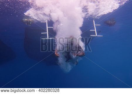 Scuba Diver Jumping In To The Sea, The Boat Silhouette Above Him.