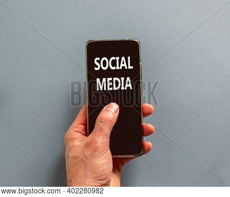 Social Media Symbol. Male Finger Clicks On Smartphone Screen With A Words 'social Media' On The Beau