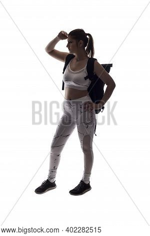 Backlit Silhouette Of A Female Model Posing As A Hiker On A White Background Wearing A Backpack.  Th