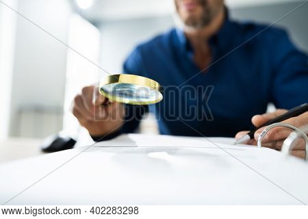 Fraud Detective Using Magnifying Glass Or Loupe