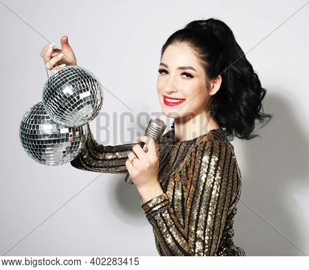 Party photo of young sensual brunette woman wearing evening dress and holding disco balls. Holiday concept.