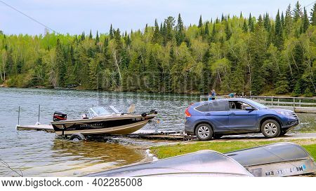 Clearwater Co, Mn - 23 May 2020: Fishing Boat With Outboard Motor On A Trailer Is Pulled Out Of The