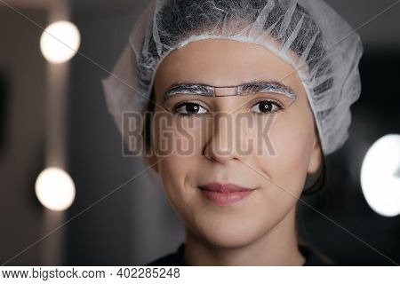 Close-up Of The Woman Face In Cap With White Anesthetic Cream On The Eyebrows Before The Permanent M