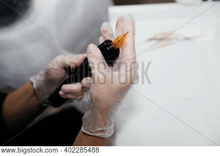 Master Beautician Makeup Artist In Gloves Holding A Tattoo Machine With New Orange Nozzle. Pigment T