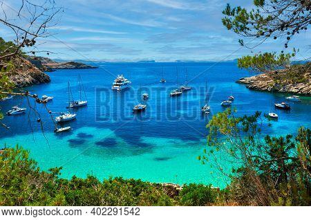 Sailboats At Cala Salada Lagoon. Bright Green Water View, Cloudy Sky, Idyllic Scenery. Ibiza, Balear