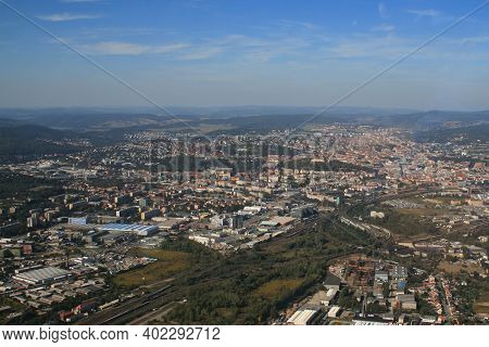 View From The Plane On The City Of Brno In The Czech Republic In Europe. In The Background Is A Blue