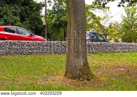 Separation Of The Street From The Park Area. A Fragment Of A Fence Made Of Gabions.