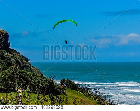 Para Glider Soars Over The Beach, Waves And Hills At Murawai Beach, Auckland, New Zealand