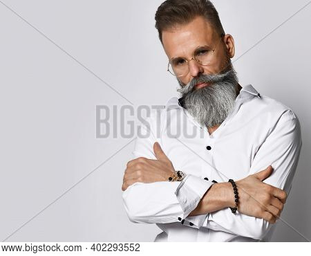 Confident Serious Stylish Mature Grey-haired Bearded Hipster Man In Eyewear Keeping Arms Crossed Loo
