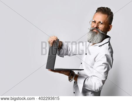 Side View Of A Business And Fashionable Bearded Mature Man In A White Shirt With A Sly Smile Closes