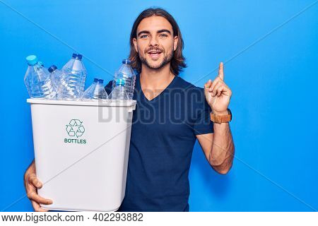 Young handsome man holding recycling wastebasket with plastic bottles surprised with an idea or question pointing finger with happy face, number one