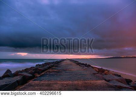 Pier to famous old farol de Portimao molhe este under gloomy sunset.Portugal