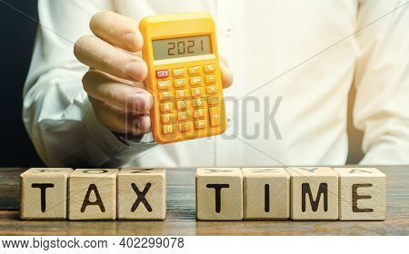 Wooden Blocks With The Word Tax Time And Taxpayer With The Inscription 2021 On The Calculator. The C