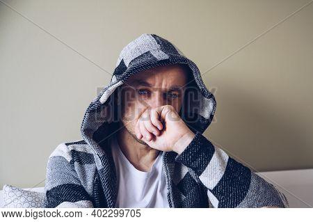 Depressed Man Sitting On Bed In Bedroom.