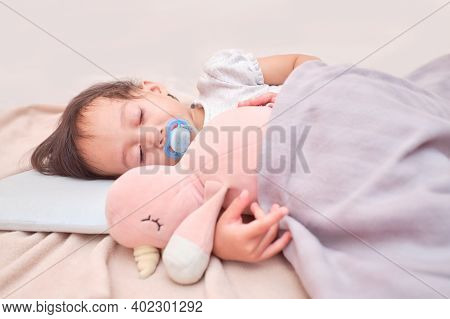 Cute Sleepy 2 Years Old Asian Infant Girl Sleeping On Soft Bedding With Pacifier, Little Kid Taking