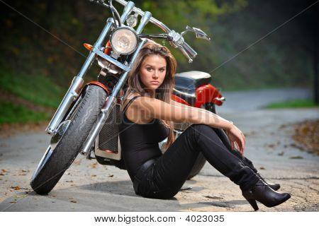 Biker Girl Sitting Next To A Bike