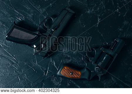 Flat Lay Of Two Pistols On Textured Black Concrete Table. Criminal Or Police Arsenal. Vintage Revolv